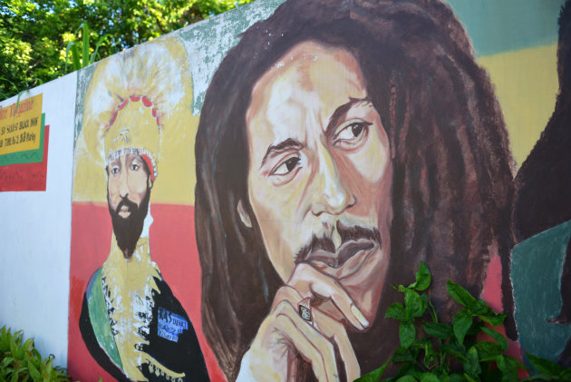 A mural depicting reggae music icon Bob Marley, right, and former Ethiopia's Emperor Haile Selassie decorate a wall in the yard of Marley's Kingston home, in Jamaica, Wednesday, Feb. 6, 2013. Relative