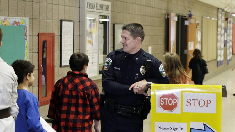 In a photo made Thursday, Feb. 21, 2013, police officer Jeff Strack smiles at children changing classrooms at Jordan Elementary School in Jordan, Minn. In what is believed to be the first of its kind nationwide, the small city south of Minneapolis is taking school security to a new level by  setting up satellite offices inside the public school buildings. (AP Photo/Jim Mone)