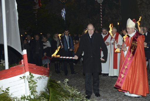 Prince Albert II of Monaco and archbishop Bernard Barsi hold torches before burning a small fisherman's boat during the traditional Sainte Devote celebration in Monaco