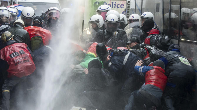 Steel workers from ArcelorMittal in Liege, Belgium, take cover as police use a water canon during a protest near the Walloon Minister President's office in Namur, Belgium, Tuesday, Jan. 29, 2013. The world's leading steel and mining company ArcelorMittal announced Thursday it will close a coke plant and six production lines in Belgium, in a move that threatens 1,300 jobs. (AP Photo/Geert Vanden Wijngaert)