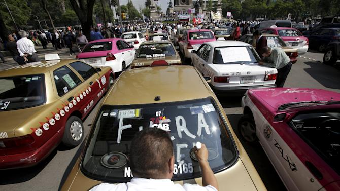 Local taxi driver paints 'Uber out' on the back windshield of his car during a protest in Mexico City