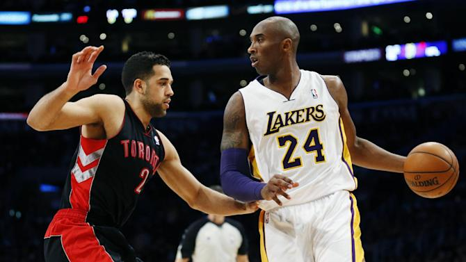 Los Angeles Lakers' Kobe Bryant dribbles the ball as he is guarded by Toronto Raptors' Landry Fields, left, during the first quarter of an NBA basketball game in Los Angeles, Sunday, Dec. 8, 2013