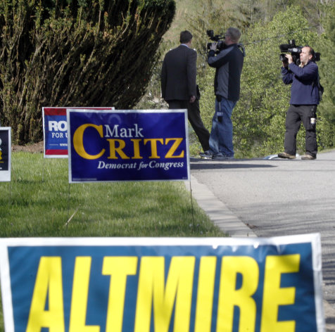 U.S. Rep. Jason Altmire, D- Pa., left, is followed by television cameras as he walks out of the polling area after he he voted in the Pennsylvania primary election on Tuesday, April 24, 2012 in McCandless, Pa., a suburb north of Pittsburgh. Altmire faces fellow U.S. Rep. Mark Critz after the Legislature and governor approved new lines combining their previously separate districts. (AP Photo/Keith Srakocic)