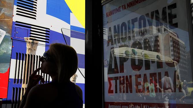 "A woman waits at a bus stop with a poster for the radical left Syriza anti-austerity party that reads ""We are opening the way to hope,"" as a tourist bus painted with the Greek flag passes by in Athens, Tuesday, June 12, 2012.  Greece faces crucial national elections on Sunday, that could ultimately determine whether the debt-saddled, recession bound country remains in the eurozone. First elections on May 6 resulted in a hung parliament. (AP Photo/Petros Karadjias)"