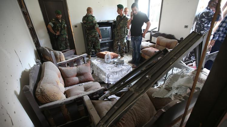 Lebanese army soldiers investigate at a damaged room where a rocket struck an apartment in a building at Chiyah district, south of Beirut, Lebanon, Sunday May 26, 2013. Rockets slammed Sunday into two Beirut neighborhoods that are strongholds of Lebanon's Hezbollah group, wounding at least 4 people, Lebanese security officials and media said. Tensions have been running high in Lebanon, and Syrian rebels have threatened to retaliate against the militant Shiite Hezbollah group for sending fighters to assist President Bashar Assad's forces in Syria. (AP Photo/Hussein Malla)