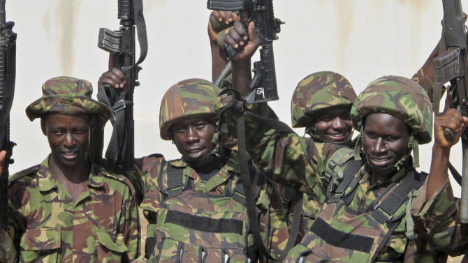 Kenyan soldiers pose for their colleagues to take pictures of them as they sing and celebrate outside Kismayo University in Kismayo, southern Somalia Tuesday, Oct. 2, 2012. Allied African troops have taken full control of Kismayo in Somalia, the last stronghold of al-Shabab Islamist rebels who have been fighting against the country's internationally backed government, a Kenyan military official said Tuesday, and Kenya Defence Forces and the Somali National Army are now patrolling the streets. (AP Photo/Josphat Kasire)