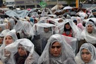 Supporters of Pakistani cleric Tahir-ul Qadri gather in the rain at a protest rally in Islamabad on January 17, 2013. Qadri called off a mass protest in Islamabad, averting a major political crisis and reaching a deal with the government that paves the way for elections within months
