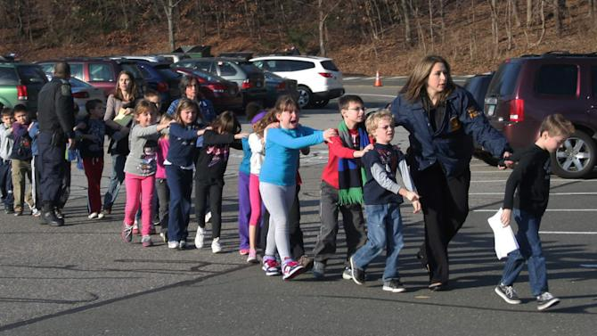 FILE - In this photo provided by the Newtown Bee, Connecticut State Police lead a line of children from the Sandy Hook Elementary School in Newtown, Conn. on Friday, Dec. 14, 2012 after a shooting at the school. In just a four-month span, New England has been the backdrop for two incidents of mass carnage - the Dec. 14, 2012 shootings in Newtown that killed 20 children and six staff members at the school, and the Boston Marathon bombings on April 15, 2013 that killed three people and injured more than 260. (AP Photo/Newtown Bee, Shannon Hicks, File) MANDATORY CREDIT: NEWTOWN BEE, SHANNON HICKS