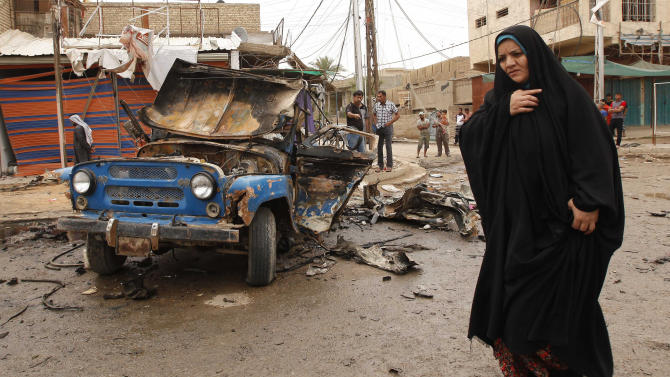 FILE - in this file photo taken on  Monday, May 20, 2013, an Iraqi woman passes by the scene of a car bomb attack in the Kamaliyah neighborhood, a predominantly Shiite area of eastern Baghdad, Iraq. More than a year after the U.S. military left Iraq, the country is reeling from its most sustained violence since 2008. Over the last two months more than 1,200 people have been killed, raising fears the country is sliding back into chaos.(AP Photo /Hadi Mizban, File)