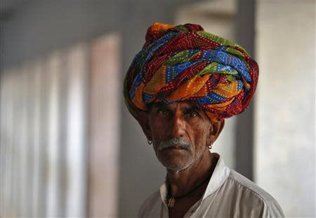 Man wearing a traditional turban waits to cast his vote outside a polling station in Ajmer