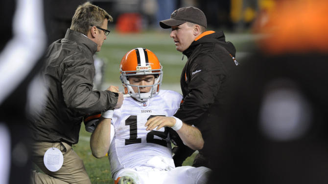 FILE - This Dec. 8, 2011 file photo shows trainers tending to Cleveland Browns quarterback Colt McCoy after he was hit by Pittsburgh Steelers outside linebacker James Harrison in the fourth quarter of an NFL football game in Pittsburgh. In a series of interviews with The Associated Press, 23 of 44 NFL players said they would try to hide a brain injury rather than leave a game. In addition, more than two-thirds of the group AP talked to wants independent neurologists on sidelines during games. (AP Photo/Don Wright, File)