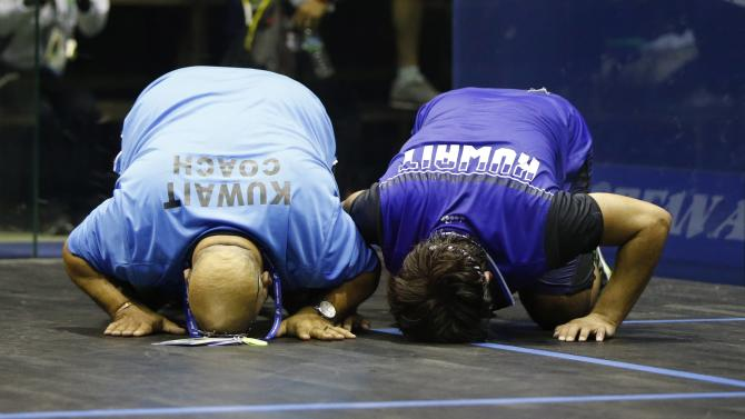 Kuwait's Abdullah Almezayen and his coach Mohamed Zahran bow in celebration after winning their men's single squash match final against India's Ghosal Saurav at the 17th Asian Games in Incheon