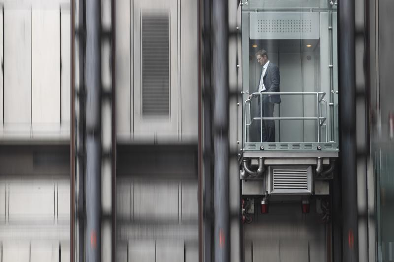 A man descends in an elevator at the Lloyds Insurance building in the City of London