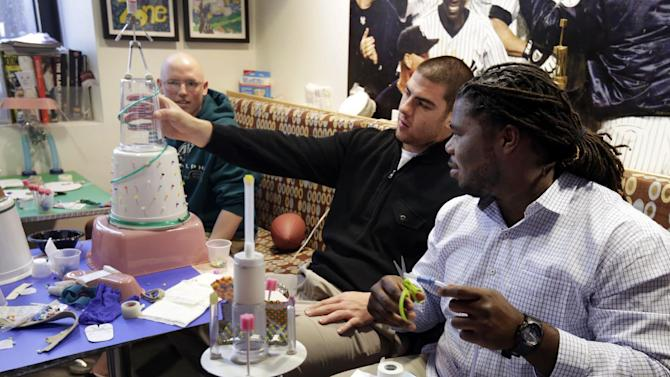 NFL draft football prospects Eric Fisher, center, of Central Michigan, and Jonathan Cooper, of North Carolina, build mock trophies from hospital materials with pediatric patient J.T. Flanagan, left, of Carmel, N.Y., in the Kravis Children's Hospital of New York's Mount Sinai Medical Center, Thursday, April 25, 2013. (AP Photo/Richard Drew)
