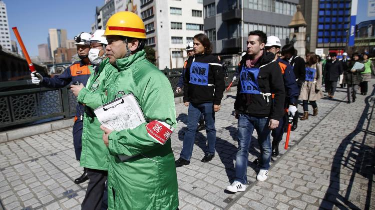 Rescue workers and local volunteer staff lead participants, acting as stranded pedestrians, to the nearest shelter during an earthquake simulation exercise at Akihabara in Tokyo
