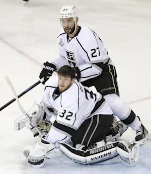 Kings goalie Jonathan Quick loses his mask as defenseman Alec Martinez helps defend against the Rangers during Game 3 of the Stanley Cup final Monday in New York. (AP)