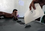 "A Syrian voter casts his ballot for the parliamentary elections at a polling station in Damascus. Syrians voted on Monday in the country's first ""multiparty"" parliamentary election in five decades, held against a backdrop of violence and dismissed as a sham by the opposition"