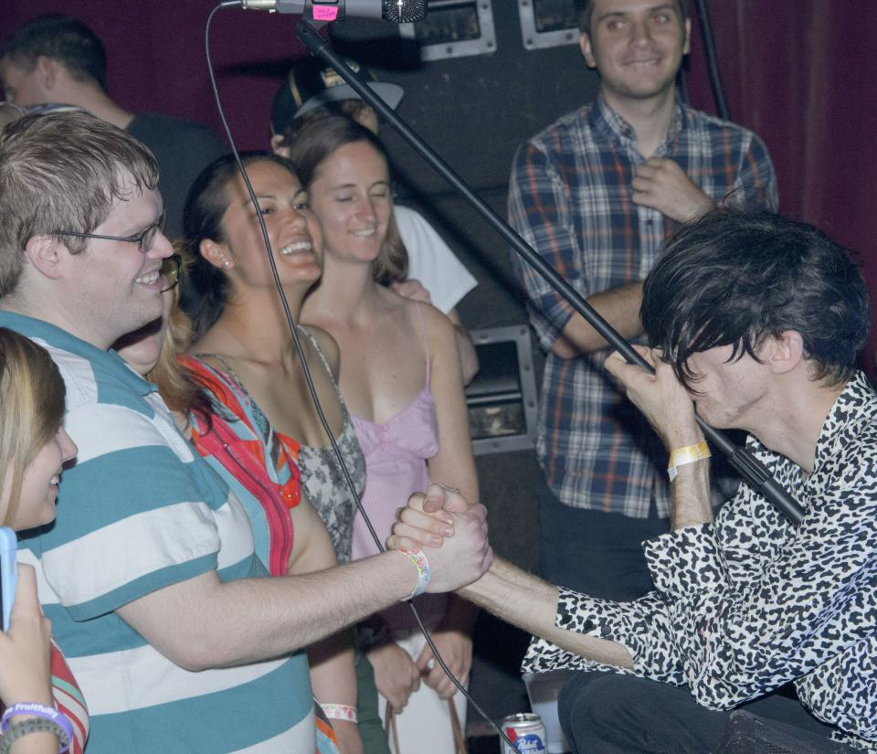 Bradford Cox gets close to fans while playing with the indie rock group Deerhunter, perform at One Eyed Jack's in the French Quarter in New Orleans, Monday, April 29, 2013. (AP Photo/Matthew Hinton)