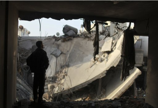 Palestinian man looks at destroyed house after Israeli air strike in Gaza City