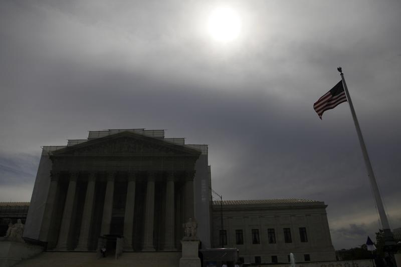 The sun shines through cloud cover above the U.S. Supreme Court building in Washington