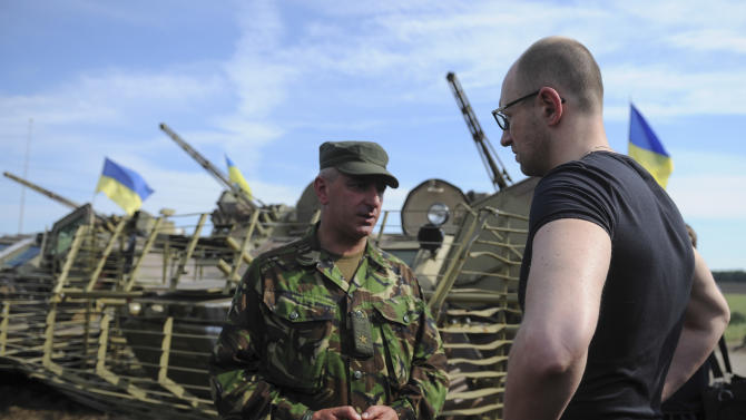 Ukrainian Prime Minister Arseniy Yatsenyuk, right, talks to an officer during inspection of a Ukrainian Army position outside the eastern town of Slovyansk, Ukraine, Wednesday, July 16, 2014. Yatsenyuk hopes to restore the infrastructure in Donetsk and Lugansk regions from state budget, thanks to private investors and international aid, he said during his visit to the Slovyansk on Wednesday. (AP Photo/Andrew Kravchenko, Pool)