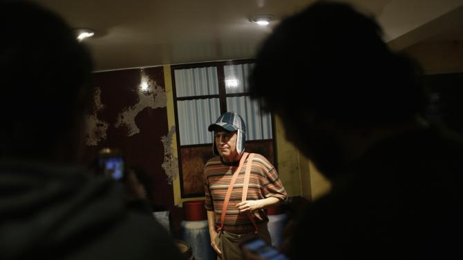 Visitors take pictures of a wax figure of El Chavo del Ocho, portrayed by comedian Roberto Gomez Bolanos at the wax museum in Mexico City