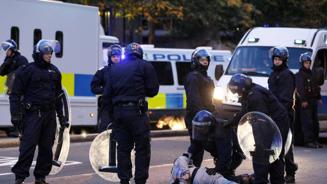 Police make an arrest during the second night of civil disturbances in central Birmingham, England, Tuesday, Aug. 9, 2011. Britain began flooding London's streets with 16,000 police officers Tuesday, nearly tripling their presence as the nation feared its worst rioting in a generation would stretch into a fourth night. The violence has turned buildings into burnt out carcasses, triggered massive looting and spread to other U.K. cities. (AP Photo/Tim Hales)