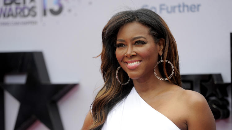 "FILE - This June 30, 2013 file photo shows TV personality Kenya Moore at the BET Awards in Los Angeles. Moore says she's seriously considering leaving ""The Real Housewives of Atlanta"" after her televised brawl with co-star Porsha Williams. Williams surrendered last week to authorities and was charged with a misdemeanor charge of battery for the fight, which was televised as part of the Bravo show's reunion special on Sunday, April 20. (Photo by Chris Pizzello/Invision/AP, File)"