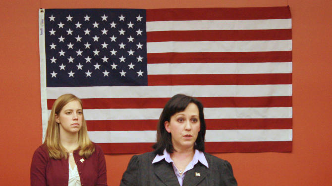 This Nov. 27, 2012, handout photo provided by the ACLU of Northern California shows Maj. Mary Jennings Hegar, accompanied by Marine Capt. Zoe Bedell, left, speaking in San Francisco. Hegar, a California Air National Guard pilot who served three tours in Afghanistan, said excluding women from a draft reinforces a stereotype that they are less capable than men and need to be protected.    (AP Photo/Gigi Pandian, ACLU of Northern California)