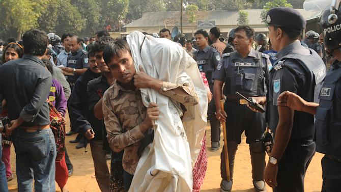 A Bangladeshi man carries the body of his relative killed in a fire at a garment factory outside Dhaka, Bangladesh, Sunday, Nov. 25, 2012. At least 112 people were killed late Saturday night in a fire that raced through the multi-story garment factory just outside of Bangladesh's capital, an official said Sunday. (AP Photo/Hasan Raza)