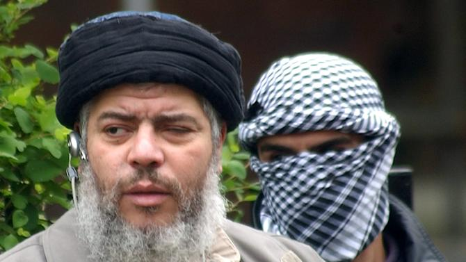FILE - This is a  Friday, April 30, 2004. file photo of  Muslim cleric Abu Hamza al-Masri, as he arrives with a masked bodyguard, right, to conduct Friday prayers in the street outside the closed Finsbury Park Mosque in London,  Radical Muslim cleric Abu Hamza al-Masri has lost a court appeal to be extradited to the United States to face terrorism charges, including allegedly trying to set up an al-Qaida training camp in rural Oregon, officials said Monday Sept. 24, 2012 . The European Court of Human Rights gave its final approval for the cleric's extradition Monday, ending a long-running legal battle. The decision means that al-Masri, considered one of Britain's most notorious extremists, could be deported within weeks. (AP Photo/Max Nash, File )