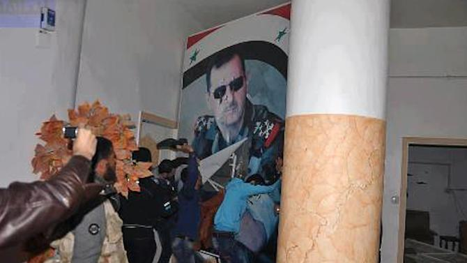 Citizen journalism image provided by Coordination Committee in Kafr Susa which has been authenticated based on its contents and other AP reporting, shows people tearing down a huge poster of President Bashar Assad and hitting it with their shoes, in Raqqa, Syria, Monday, March. 4, 2013. The activists said the picture was taken inside the Air Force Intelligence headquarters in Raqqa. (AP Photo/Coordination Committee In Kafr Susa)
