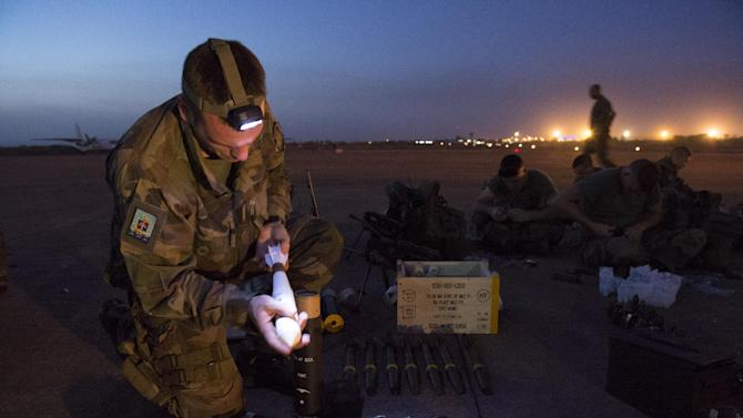 """In this picture dated Sunday, Jan. 13, 2013 and released by the French Army Communications Audiovisual office (ECPAD), a French soldier of the 2nd Marine Infantry Regiment based in Le Mans, western France, prepares ammunition before distribution at Bamako airport, Mali. An official at France's Defense Ministry says the country will """"gradually deploy"""" a total of 2,500 troops to Mali, and the French president says the military operation will last until security has been restored and African forces are ready to take charge. (AP Photo/Arnaud Roine, ECPAD)"""