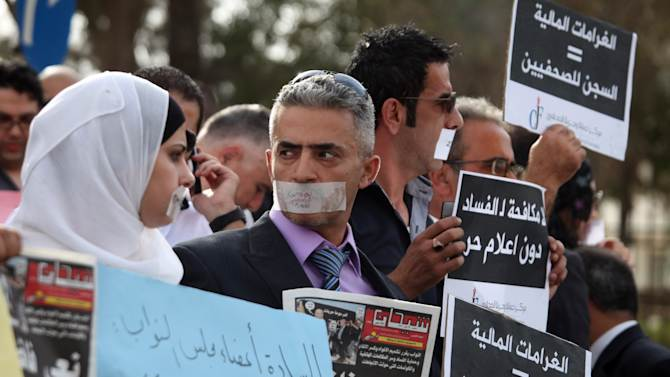 """FILE --  In this Thursday Sept. 29, 2011 file photo, Jordanian journalists protest in front the Jordanian House of Parliament, symbolically wearing tape over their mouths, as they protest over proposed changes to the anti-corruption law they believe will muzzle press freedoms, in Amman, Jordan. Jordan's prime minister Abdullah Ensour told a meeting of the Geneva-based International Press Institute (IPI) that Jordan has """"come a long way"""" in improving both legislation governing press freedoms and the standards of a national media still reeling under long years of state censorship. Nidal Mansour, head of the Amman-based Center for Defending Freedom of Journalists --IPI's hosting partner -- said that the press law enacted last year was designed to muzzle press freedoms. (AP Photo/Mohammad Hannon, File)"""
