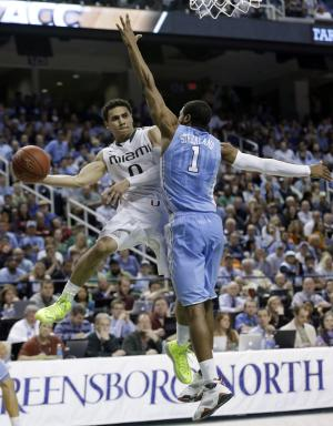 Miami's Shane Larkin (0) passes the ball around North Carolina's Dexter Strickland (1) during the second half of an NCAA college basketball game in the championship of the Atlantic Coast Conference tournament in Greensboro, N.C., Sunday, March 17, 2013. (AP Photo/Gerry Broome)