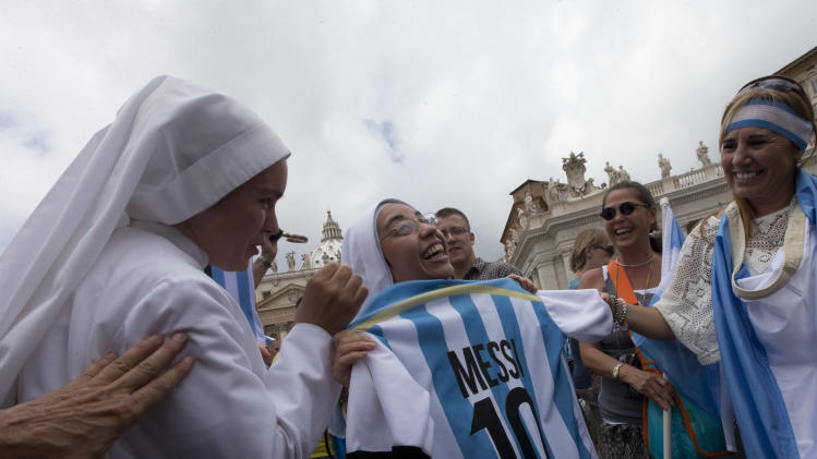 "Argentine nuns show an Argentina soccer team jersey with the name and number of Lionel Messi before Pope Francis delivers the Angelus prayer in St. Peter square at the Vatican, Sunday, July 13, 2014. The Argentine-born, football-loving pontiff pledged neutrality, promising not to pray for any team. However, Francis did tweet on the eve of the final: ""The World Cup allowed people from different countries and religions to come together."" (AP Photo/Alessandra Tarantino)"