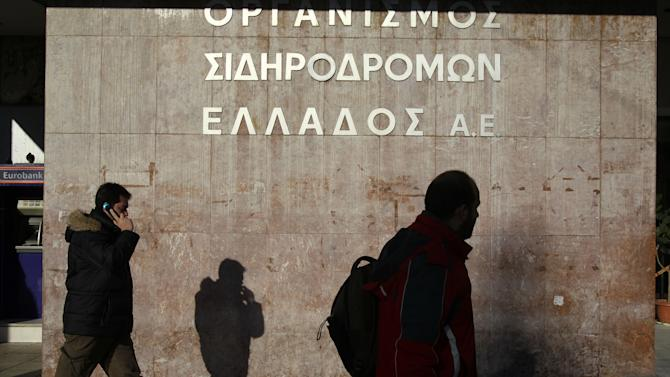 Pedestrians pass under the sign of Greece's railways at the closed central train station during a 24-hour strike in Athens, Wednesday, Feb. 20, 2013. Unions have launched another general strike against austerity measures in Greece, amid predictions unemployment in the crisis-hit country will reach 30 percent this year. (AP Photo/Thanassis Stavrakis)