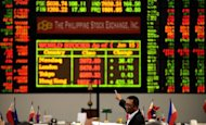 A Filipino trader points at the Philippine Stock Exchange (PSE) in Manila in June 2012. The Philippine central bank cut interest rates on Thursday for the third time this year, citing the domestic economy&#39;s need for extra help amid an uncertain global climate