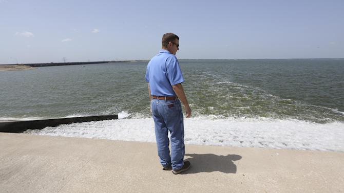 In this photo Wednesday, July 9, 2014, Chris Zachry, wetlands project manager for the Tarrant Regional Water District, watches clean water from a man made wetland project flow into the Richland Chambers Reservoir near Fairfield, Texas. As slow-moving, turbid water snakes through a man-made wetland, phosphorous and nitrates are slowly filtered out through shallow ponds full of lush vegetation and water birds until, a week later, the water runs clear as a creek directly into a North Texas drinking supply. (AP Photo/LM Otero)