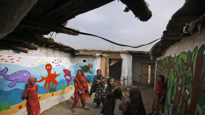 Pakistani schoolgirls, who were displaced with their families from Pakistan's tribal areas due to fighting between militants and the army, play in their school yard during a break, in a poor neighborhood on the outskirts of Islamabad, Pakistan, Friday, Oct. 19, 2012. A teenage activist recently shot and critically wounded by the Taliban risked her life to attend school, but the threat from the militant group is just one of many obstacles Pakistani girls face in getting an education. Others include rampant poverty, harassment and the government's failure to prioritize education spending. (AP Photo/Nathalie Bardou)