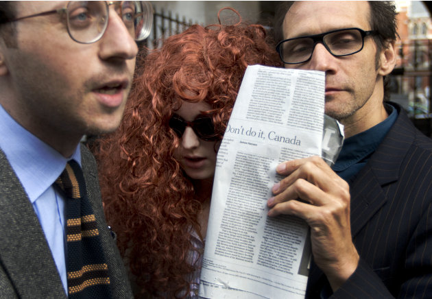 A woman dressed up in a wig to look like Rebecca Brooks, center, the former Chief Executive Officer of News International, pretends to be her arriving with two men at the Leveson media ethics inquiry,