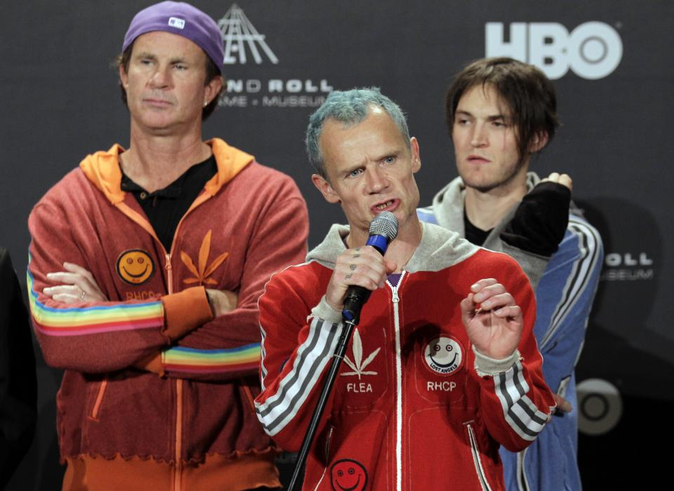 "Red Hot Chili Peppers bassist Mike ""Flea"" Balazary, center, answers question in the press room before induction into the Rock and Roll Hall of Fame Friday, April 13, 2012, in Cleveland. Drummer Chad Smith, back left, and guitarist Josh Klinghoffer listen in. (AP Photo/Amy Sancetta)"