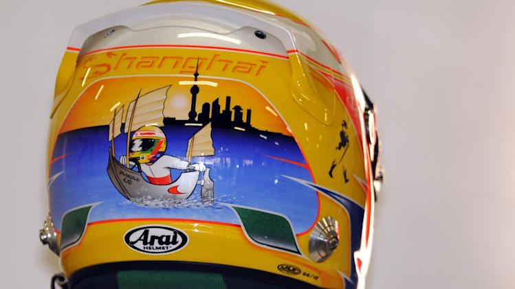 McLaren Mercedes driver Lewis Hamilton of Britain wears a Shanghai helmet for the first practice session for Formula One's Chinese Grand Prix at the Shanghai International Circuit on April 13, 2012.    AFP PHOTO/Peter PARKS (Photo credit should read PETER PARKS/AFP/Getty Images)