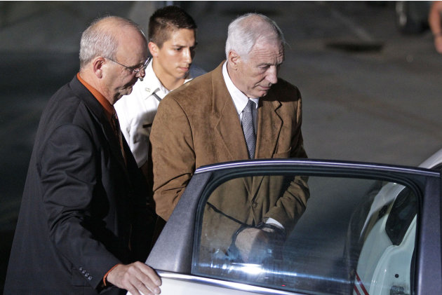 Former Penn State University assistant football coach Jerry Sandusky, right, is escorted by Centre County Sheriff Denny Nau, left, as he is taken into custody at the Centre County Courthouse after bei