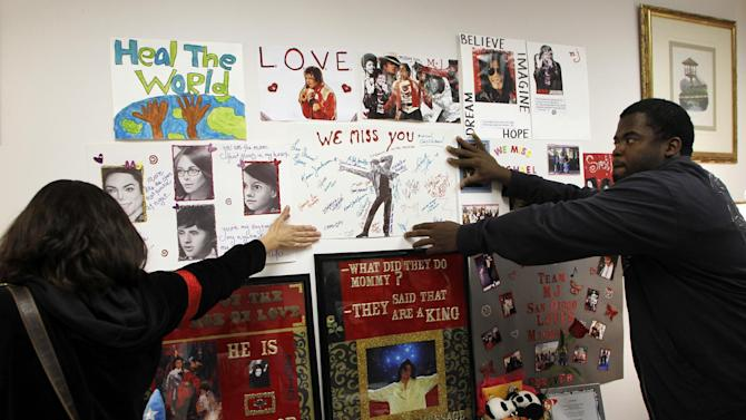 Michael Jackson fans Kim Lemieux, left, and Michael Craig hang a poster at a memorial where the headboard of the bed that Jackson was in on the day he died would have been placed in an exhibition at Julien's Auctions during a private preview of contents of 100 North Carolwood Drive, the home where Michael Jackson was living when he died, on Sunday, Dec. 11, 2011 in Beverly Hills, Calif. The carved headboard seen in evidence photos during the criminal trial of Jackson's physician was removed from the auction's lots at the request of Jackson's estate. (AP Photo/Danny Moloshok)