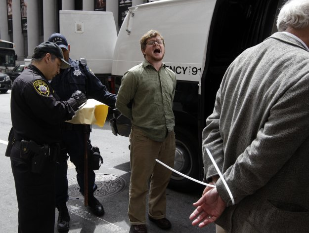 A demonstrator is arrested outside of the Wells Fargo shareholders meeting in San Francisco, Tuesday, April 24, 2012. Police were guarding the entrance to the annual meeting of Wells Fargo shareholders on Tuesday as protesters associated with the Occupy Wall Street movement protested the gathering. (AP Photo/Marcio Jose Sanchez)