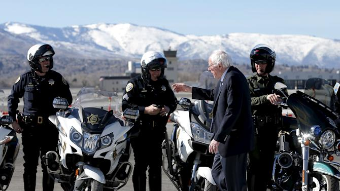 U.S. Democratic presidential candidate Bernie Sanders greets police officers from a motorcade before boarding his campaign plane in Reno
