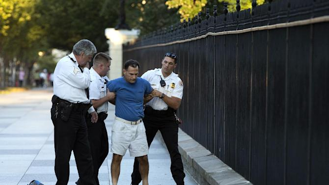 A man is taken into custody by uniformed Secret Service Police on Pennsylvania Avenue outside the White House on Monday, Sept. 16, 2013, in Washington. The Secret Service arrested the man for tossing lit firecrackers over the White House fence. (AP Photo/ Evan Vucci)