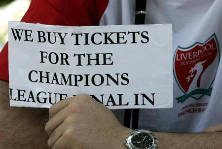 A Liverpool fan holds a placard seeking tickets for the Champions League final in Athens May 22, 2007. REUTERS/Yiorgos Karahalis/Files
