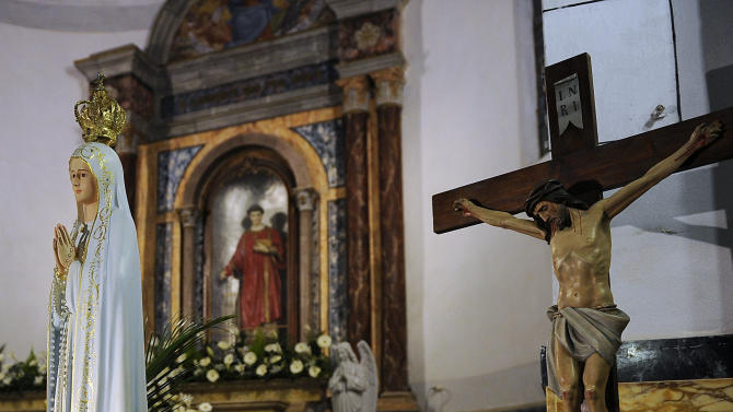 A fragment of rock which perforated the hull of the Costa Concordia cruise ship is placed near a statue of the Virgin Mary and a crucifix in a church of the Tuscan Island Isola del Giglio, Italy, Saturday, Jan. 12, 2013. More time and money will be needed to remove the Costa Concordia cruise ship from the rocks off Tuscany where it capsized last year, in part to ensure the toxic materials still trapped inside don't leak into the marine sanctuary when it is righted, officials said Saturday. On the eve of the first anniversary of the grounding, environmental and salvage experts gave an update on the unprecedented removal project under way, stressing the massive size of the ship — 112,000 tons, its precarious perch on the rocks off the port of Giglio island and the environmental concerns at play. (AP Photo/Gregorio Borgia)